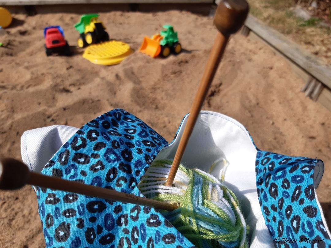 Käsityöpussi hiekkalaatikon reunalla.