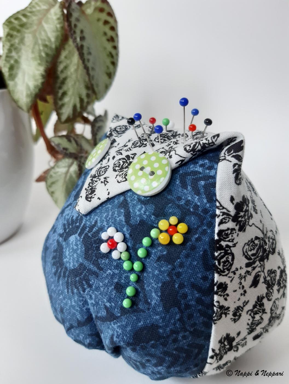 Pöllön mallinen neulatyyny viherkasvi taustana.