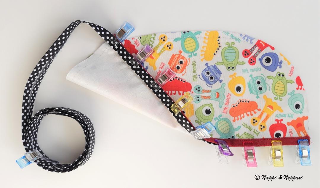 Ruokalapun tasku, jonka yläosaan on kiinnitetty vinonauha ompelua varten.