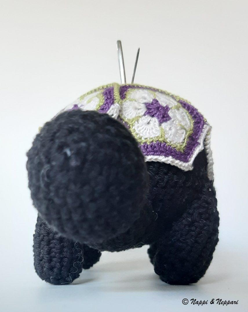 Kilpikonnan mallinen virkattu neulatyyny edestäpäin kuvattuna.