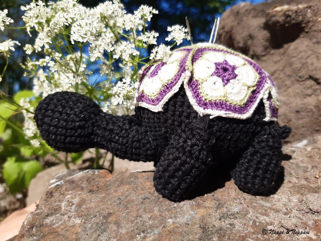 Kilpikonnan mallinen virkattu neulatyyny kivellä.